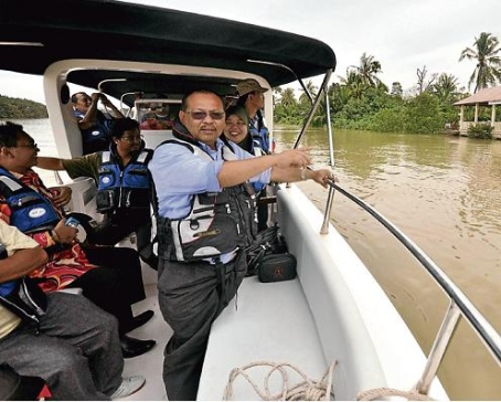 Abdul Razak Minhat on a boat ride as he identifies suitable areas for development. Pic by Shaiffulazhar Misri