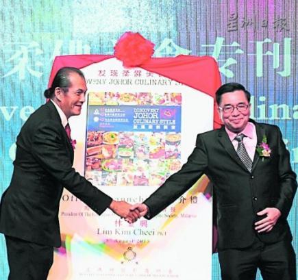 《發現柔佛美食》紀念專刊出版了!陳寬(左)和薛錦棋聯合主持推介禮后握手互道賀。