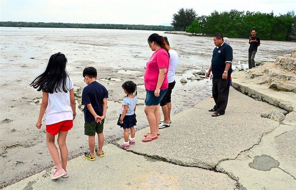 A day by the beach:A group of local folk looking at mudskippers during low tide at the Tanjung Emas beach in Muar.